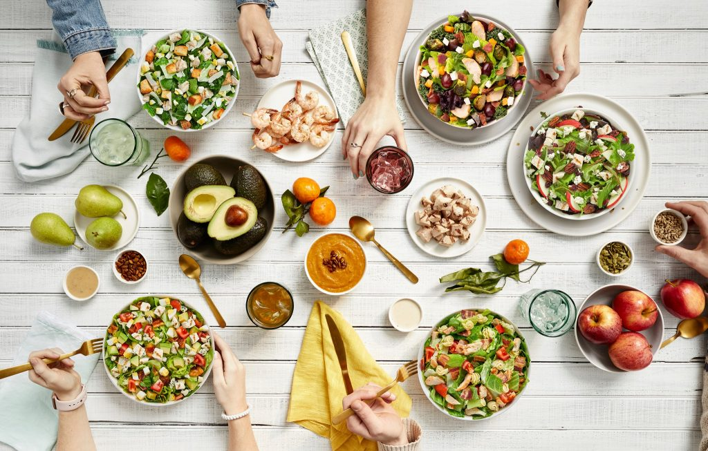 Table setting of people eating salads