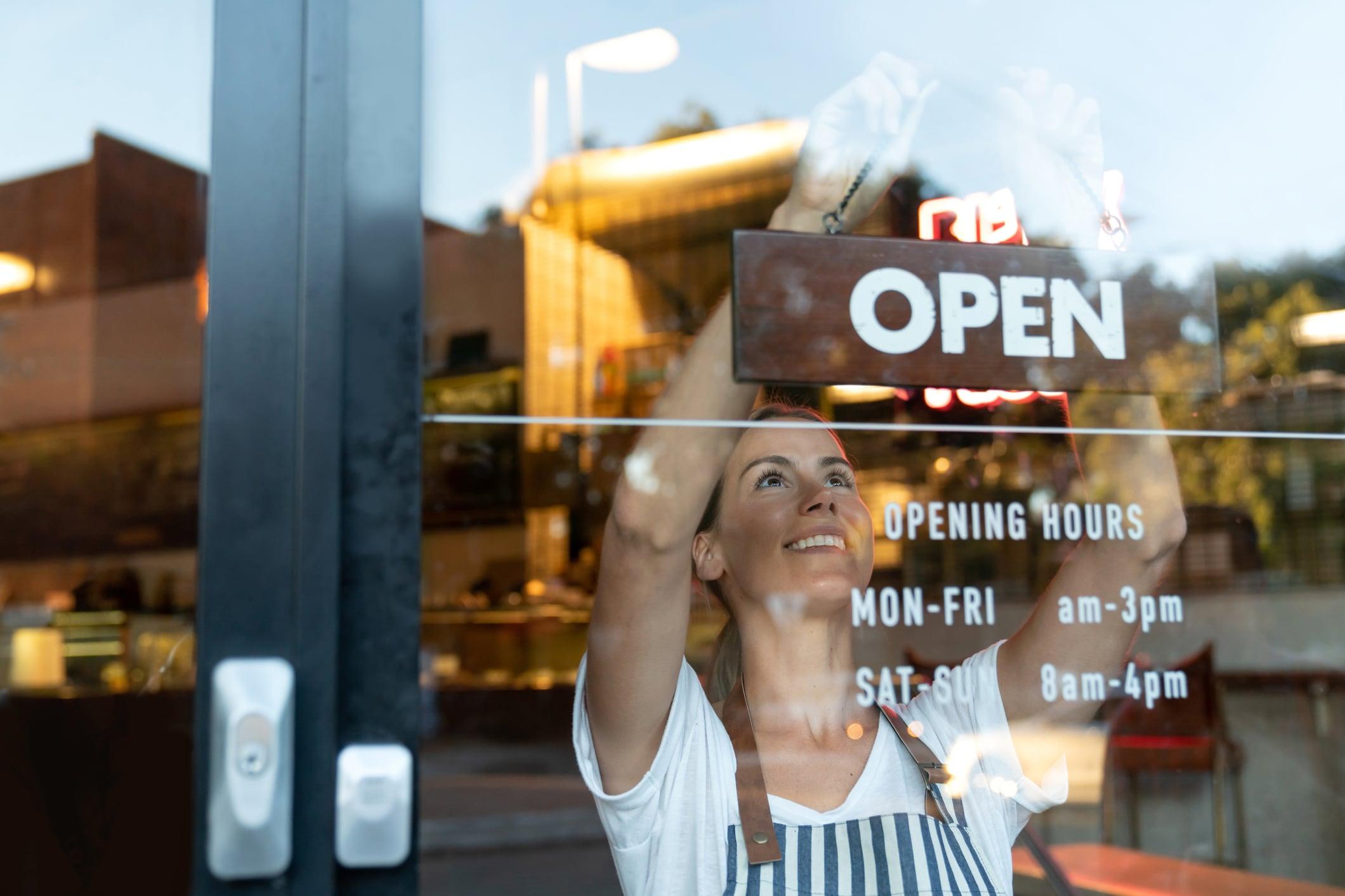 Women handing Open sign in window